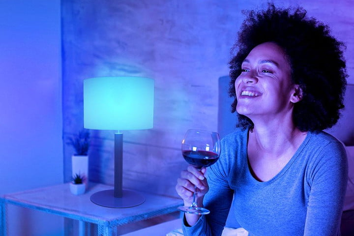 Woman having glass of wine with Govee Smart LED light bulb on.